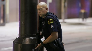 A Dallas policeman keeps watch on a street in downtown Dallas.