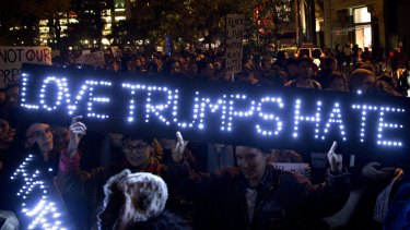 """Illuminating message: Demonstrators hold a neon sign reading """"Love Trumps Hate"""" during a protest at Union Square in New York."""