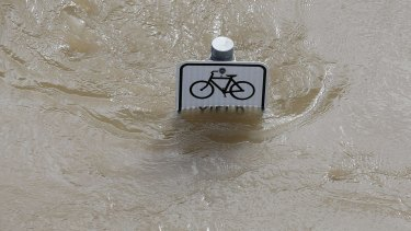 Water is seen at the top of a sign along a bike path near Memorial Drive in Houston.