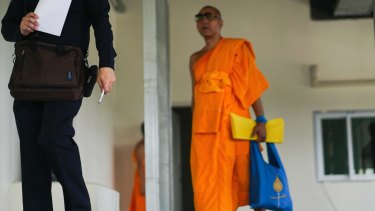 A monk follows an officer inspecting a medical center on the Wat Dhammakaya temple.