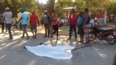 People stand by the body of a man who died when a bus crashed into a crowd watching street musicians in Haiti.
