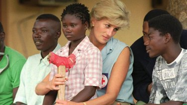 Diana talks to amputees who lost limbs to land mines, in Angola in 1997.