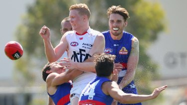 Crunch time:  Clayton Oliver rids possession as Bulldog defenders apply pressure.