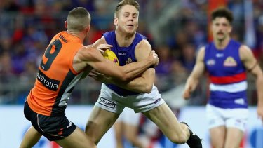 Giving it everything: Lachie Hunter of the Bulldogs is tackled by Tom Scully of the Giants.