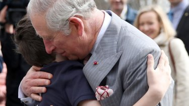 Prince Charles receives a hug from Valentin Blacker, son of William Blacker who is a local conservationist, during a walking tour of the Old Town in Bucharest.