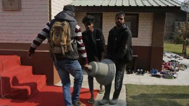 People carry an old bell that was damaged in an incident of arson in 1967 after removing it at the Holy Family Catholic Church in Srinagar, Indian controlled Kashmir.