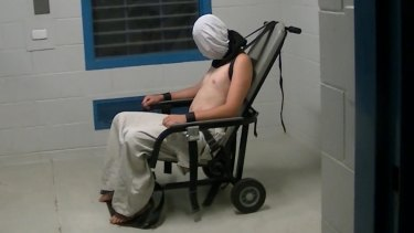Dylan Voller is hooded and strapped to a restraining chair in the footage aired on Four Corners.