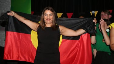 New Indigenous MP Lidia Thorpe, draped in the Aboriginal flag, celebrates her win in Northcote.