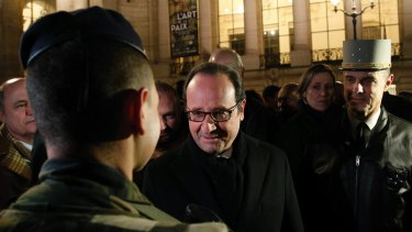 France's President Francois Hollande smiles at a French soldier as he visits the security measures at the Champs Elysees in Paris.