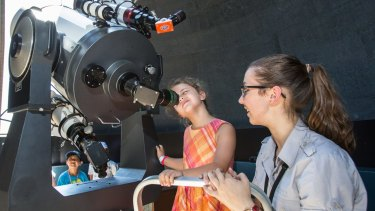 Aboriginal astronomy tour guide Kirsten Banks assists Tia, 6, at the Sydney Observatory this year.