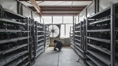 A technician inspects bitcoin mining machines at a mining facility in inner Mongolia.