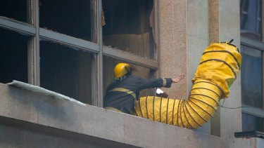 A fireman adjusts the vent to allow smoke to escape from the Resorts World Manila.