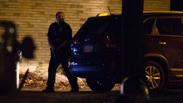A police officer hides behind a car as the crowd gathers.