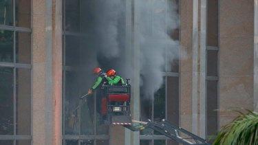 Firemen break the glass panels to allow the smoke to escape from the Resorts World Manila complex.