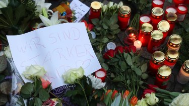 """A message reading """"We are stronger"""" sits amongst flowers near where the attack occurred."""