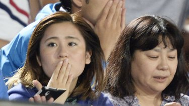 Japanese soccer fans react to a strong earthquake as they watch a J-League match in Hiratsuka, south-west of Tokyo.