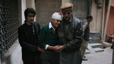 The uncle and cousin of injured student Mohammad Baqair, centre, comfort him as he mourns the death of his mother,  a teacher at the Peshawar school attacked by Taliban in December 2014.