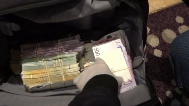 Police allegedly found large amounts of foreign currency and a gun in a bag during the raid.