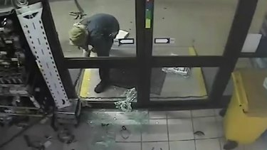 A man chains up an ATM inside the service station.