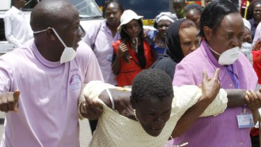 Medical staff console a woman in Nairobi after she viewed the body of a relative killed in Thursday's attack at Garissa University in north-eastern Kenya.