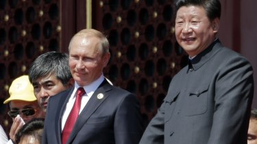 Chinese President Xi Jinping, right, and Russian President Vladimir Putin observe a military parade.