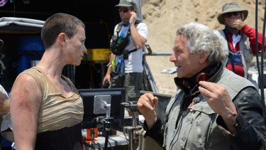 George Miller on the set of Mad Max: Fury Road with Charlize Theron.