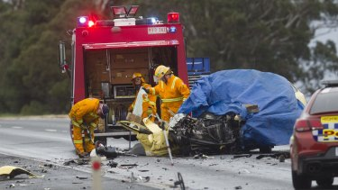 Emergency services examine the wreckage of a car that hit a truck in a head-on collision.