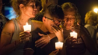 Mona Rodriguez holds her 12-year-old son, J Anthony Hernandez, during a candlelight vigil held for the victims of a fatal shooting at the First Baptist Church of Sutherland Springs.