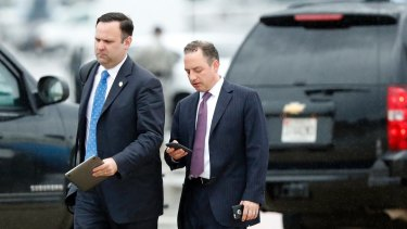 Former White House Chief of Staff Reince Priebus, with phone, walks in the rain.