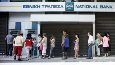 Greeks queue in front of the National Bank to use ATM.