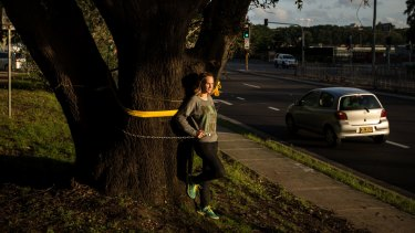 Louise Boronyak-Vasco chains herself to an old tree due to be cut down to make way for the light rail.