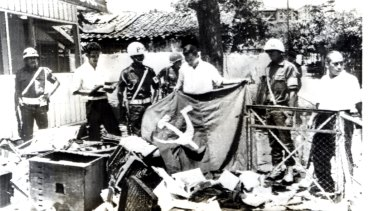 Indonesian police and a youth hold a Communist flag in the ruins of Indonesian Communist Party headquarters in Jakarta after it was ransacked by anti-communist demonstrators in 1965.