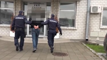Serbian authorities handcuff one of three Australian men arrested in a Belgrade hotel in connection to a cocaine importation.
