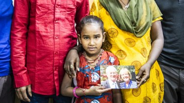 Divya, 8, holds a photo of Dick and Pip Smith.