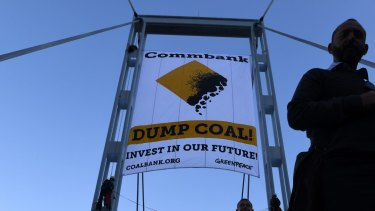 Two activists unveil a banner protesting coal financing by the Commonwealth Bank in Sydney, Friday, May 5, 2017.