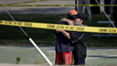 Two people hug in front of police tape following a shooting during a congressional baseball practice near the Eugene Simpson Stadium Park in Virginia on Wednesday.