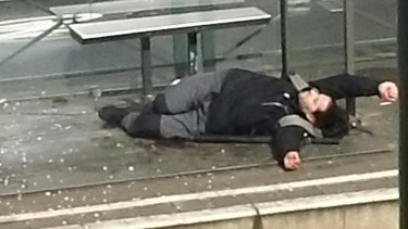 An injured man lays on the ground at a tram stop in Brussels, Belgium, on Friday.
