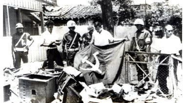 Indonesian police hold a communist flag in the ruins of Indonesian Communist Party  House in Jakarta after it was ransacked by anti-communist demonstrators in 1965.