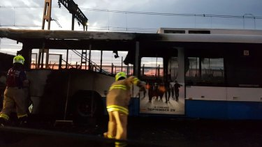 Firefighters work on the charred remains of the bus.
