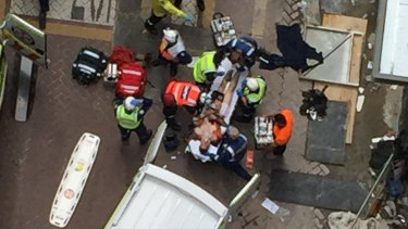 Paramedics take a worker from a North Sydney building site to hospital after a crane collapse.