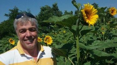 Ballarat man Lawrence Richmond in a sunflower crop growing on a farm in Ukraine.
