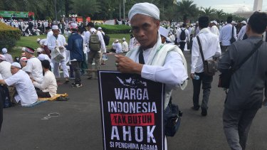 "A protester carries a sign that reads ""The people of Indonesia do not need Ahok"" at a December rally against the governor in Jakarta."