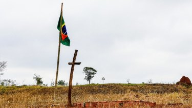 A bloodied flag, a cross and a brick grave mark the place where Clodiode dos Santos, 26, was killed.