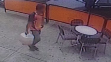 CCTV footage showing a man walking back to the bank with a container after he visited a service station.