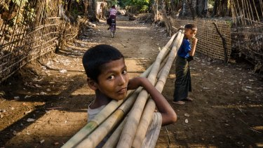 Boys carry bamboo stalks at the Sin Tet Maw camp for internally displaced persons in Rakhine State, Myanmar.