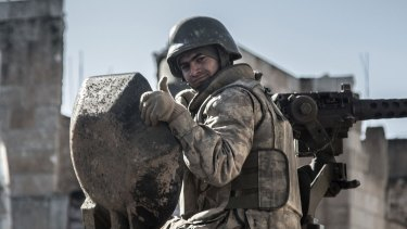 A Turkish soldier gives the thumbs up on Sunday on top of an army vehicle in Kobane.