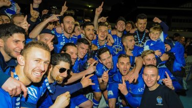 All smiles: South Melbourne players and fans celebrate after lifting another state league trophy.