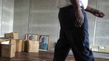 A worker walks past photographs of  Robert Mugabe at a government building in Harare.
