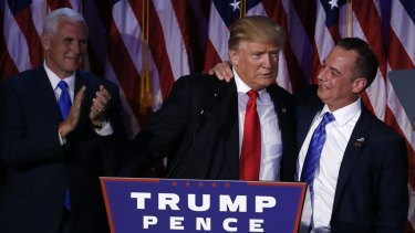 US President-elect Donald Trump is embraced by Reince Priebus, chairman of the Republican National Committee, after the shock election win as Vice-President-elect Mike Pence looks on.
