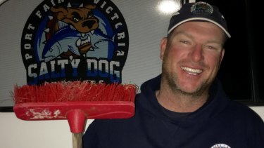 Dan Hoey with the broom he used to fend off the shark.